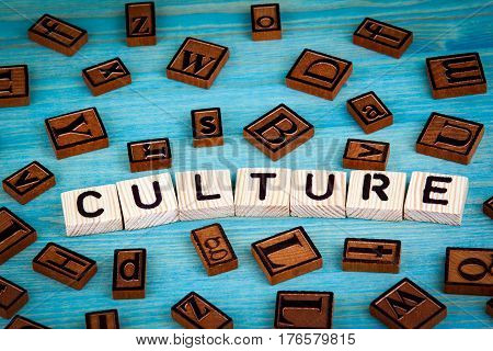 culture word written on wood block. Wooden alphabet on a blue background.