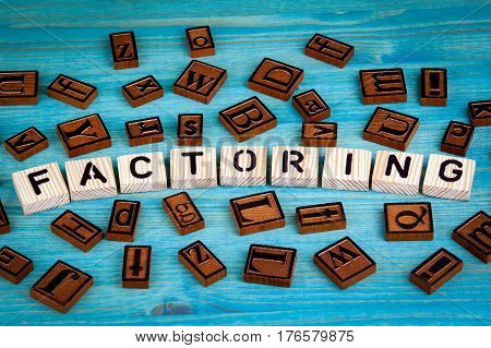 factoring word written on wood block. Wooden alphabet on a blue background.
