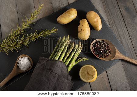 Asparagus with potatoes and spices on a slate plate
