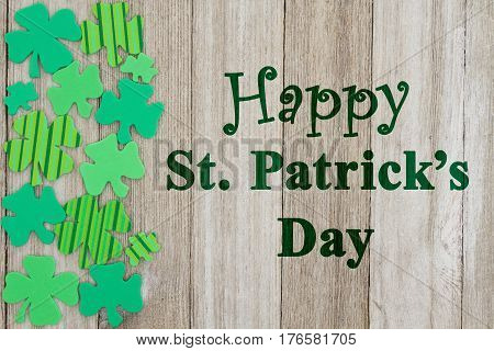 Saint Patrick's Day greeting Green shamrocks on weathered wood with text Happy St Patrick's Day