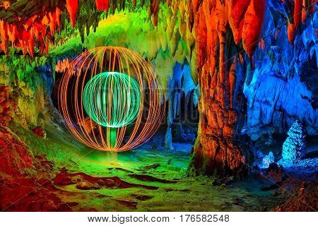 Cave interior abstract painted with colored light and a double sphere made with light on one side