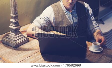 Closeup of elegant tattooed man working at home on laptop while sitting at the wooden table.Using modern computer for research new startup ideas.Concept of business people work.Blurred background