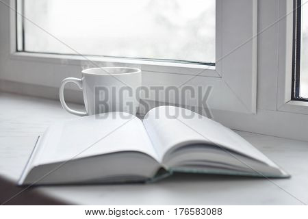 Cozy home still life: cup of hot coffee or tea and opened book on windowsill. Education concept, free copy space.