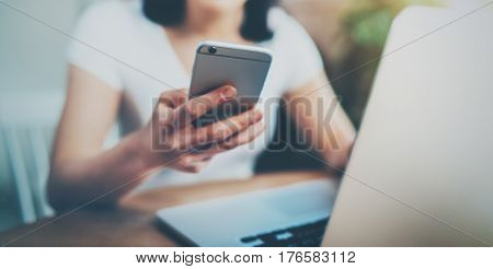 Young Asian woman spending rest time at home and using smartphone for texting message.Selective focus on mobile phone. Blurred background