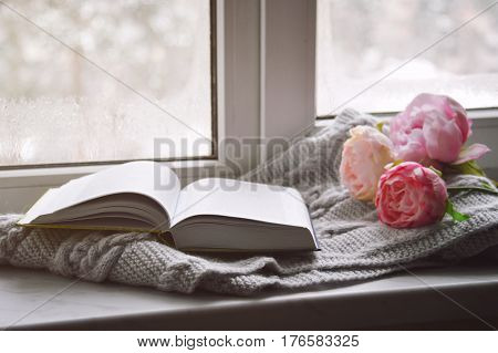 Cozy home still life: spring flowers and opened book with warm plaid on windowsill. Springtime concept, free copy space.