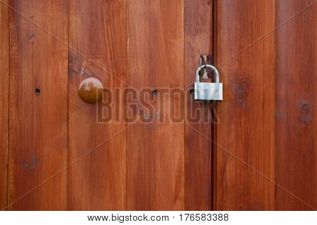 Wooden door with a padlock and knob closeup