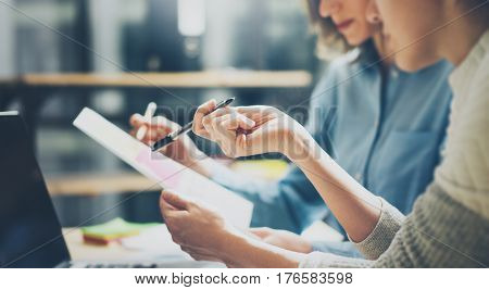Group of young coworkers working together in modern office.Woman talking with colleague about new startup project.Business people brainstorming concept.Selective focus.Horizontal, blurred