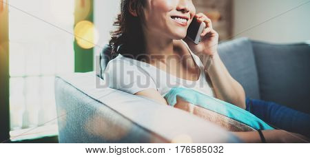 Portrait of young smiling Asian woman sitting on sofa at home, wearing white tshirt and talking smartphone.Horizontal blurred, flares effect