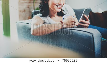 Young smiling Asian woman spending rest time at home on sofa, holding ceramic cup at hand and using smartphone for video conversation with friends.Blurred background, crop.Wide