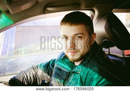 Young Male Driver Sits Holding His Hand Behind The Wheel In The Salon Of His Car, A Happy Look Of A