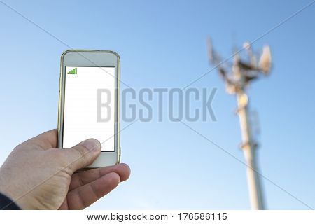 Man holds mobile phone on hand pointing to telephony antenna or base station