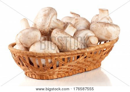 Champignon mushrooms in a wicker basket isolated on white background.