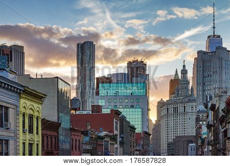 Colorful sunset behind the downtown skyline buildings of Chinatown in Manhattan New York City