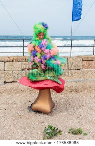 Participant Of Festival Dressed As Elf Sits On Large Mushroom