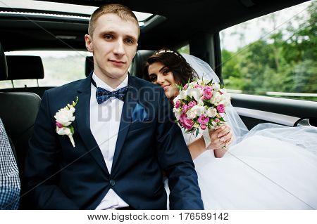 Young Stylish Wedding Couple Sitting At Car.