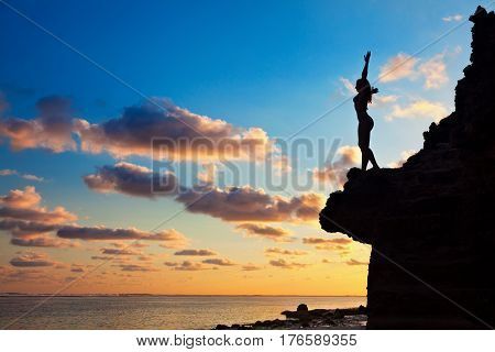 Black silhouette of happy young woman with slim body and hands up high in air on sunset sky background. Girl stand on rock top looking at ocean surf. Healthy lifestyle people on summer beach holiday.