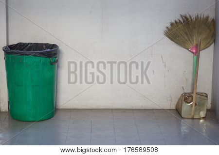 Broom with dustpan and small trash at the wall
