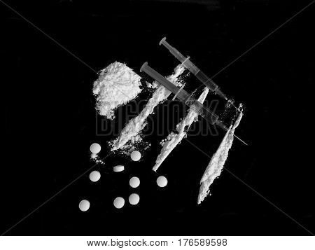 Injection syringe on cocaine drug powder lines, pile and pills on black background