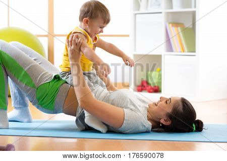 happy mother and child making healthy fitness exercises