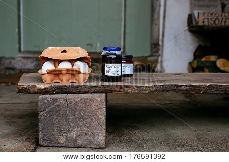Eggs and homemade jam for sale on the porch of a house in small village of Lacock, England. Buyers are asked to pay for products into honesty box.