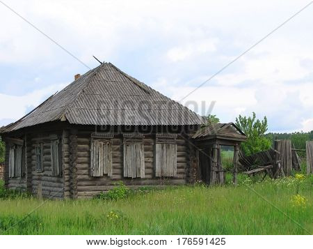 Abandoned wooden house with boarded up windows in the Russian countryside.