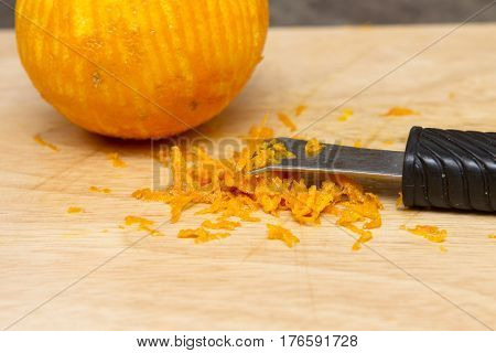 Zesting an orange on wooden table with kitchen implement.