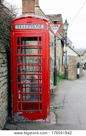Old red telephone box with paint peeling off in a small English village