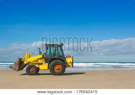Yellow bulldozer working on a beach with blue cloudy sky