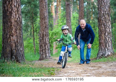Happy cute blond kid boy having fun his first bike on sunny summer day outdoors. Happy child making sports. Active leisure for children.Kid boy wear safety helmet. boy is smiling and cicling.