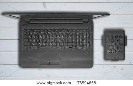 Open laptop and external hard drive lie on a light wooden background. Flat lay