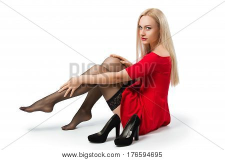 Woman in the red dress and stockings take off her shoes and have a rest after high heels - isolated on white