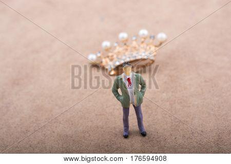 Standing man figurine beside a model crown