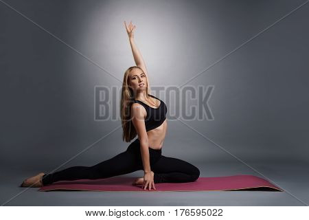 Pretty young fitness trainer in black top and leggings exercising on mat in studio