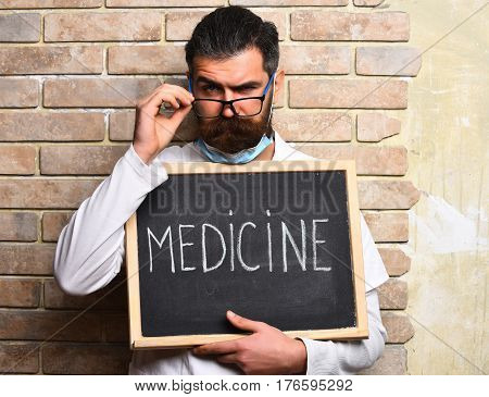 Bearded Brutal Caucasian Doctor Holding Board With