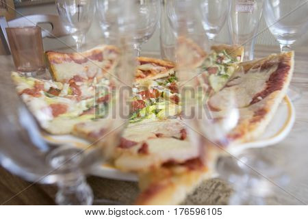 homemade pieces of pizza seen through a series of crystal glasses
