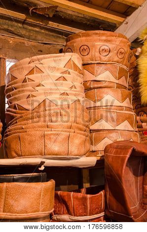 Handmade leather poufs stacked high in small traditional craft shop in soukh of Fez, Morocco.