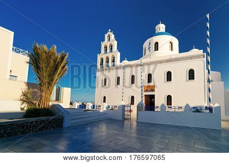 Picturesque square and white church of Panagia Platsani with blue dome in Oia or Ia on the island Santorini in the morning, Greece