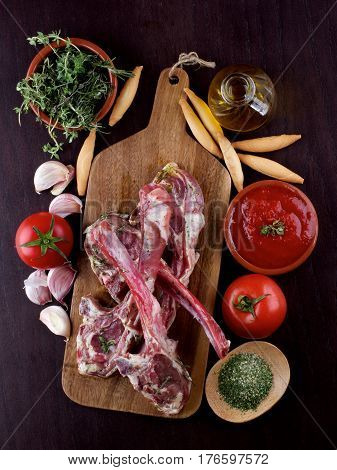 Raw Lamb Ribs with Tomatoes Spices Herbs Olive Oil and Garlic on Wooden Cutting Board closeup on Dark Wooden background. Concept Ready to Roast