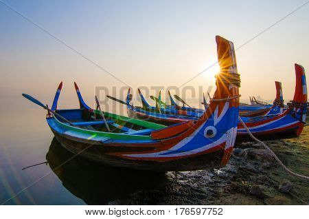 traditional boat at sunrise in Taungthaman Lake near the U Bein Bridge, Mandalay, Myanmar , selective focus, sunlight and lens flare.