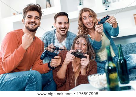 Happpy young friends playing video games at home.