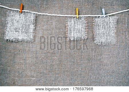 Rectangle pieces of white burlap pinned on cotton ropes as various frames on gray burlap background. Rustic style eco-friendly universal template