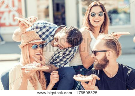 Close-up of four young cheerful people eating pizza. Group of friends taking their slices of pizza.