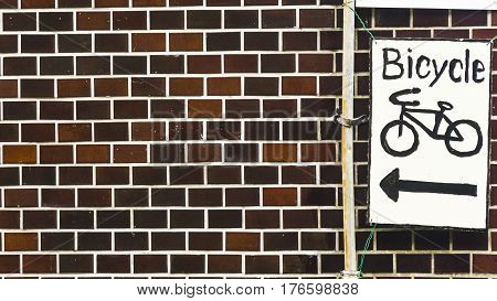 the bicycle symbol on white signage plate with the brick wall facade.