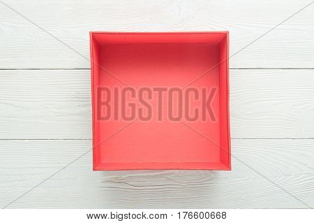 Empty red box on white wooden background. Flat lay. Top view with copy space