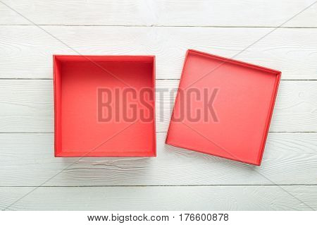 Blank red gift box with lid on white wooden background. Flat lay. View from above