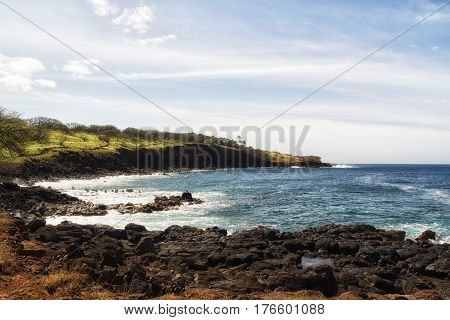 Small bay on the north west coast of the Big Island of Hawaii on a sunny day with cloud streaks.