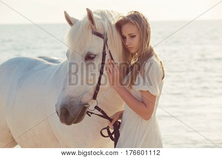 Beautiful bride in white wedding dress with horse on the beach.