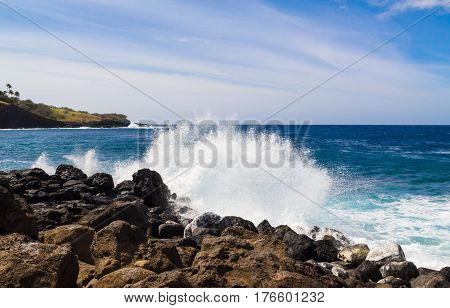 Rocky coastline of the Pacific Ocean on Hawaii Island with waves and spray on a sunny day.