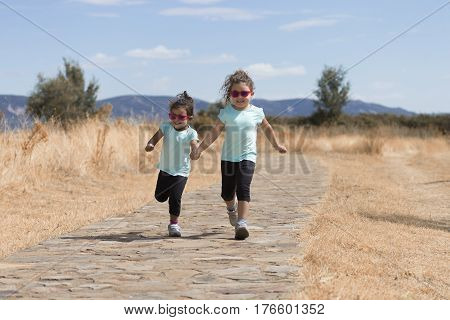 Two little cheerful girls wearing same clothing holding hands and running down rural road.