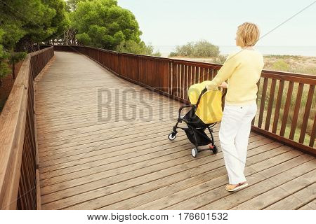 Mother pushing stroller on wooden bridge walkway. Young woman walking with a baby in stroller outdoors